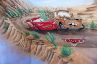 Malowanie na ścianie obrazu bajkowego przedstawiającego samochody, aranżacja pokoju dziecięcego na poddaszu