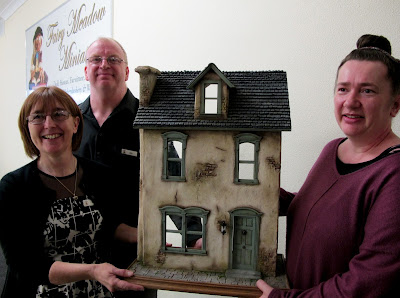 The owners of Fairy Meadow Miniatures shop presenting the prize house to the winner of the VIP opening raffle.