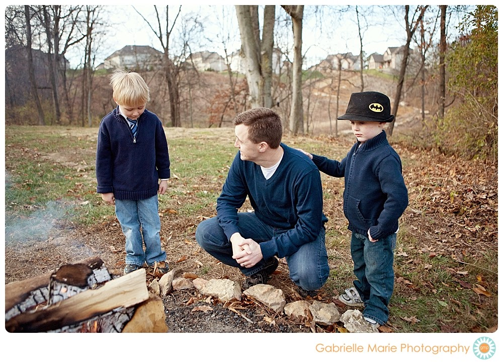 Dad and two sons stand around the fire while little boy places hand on dad's back