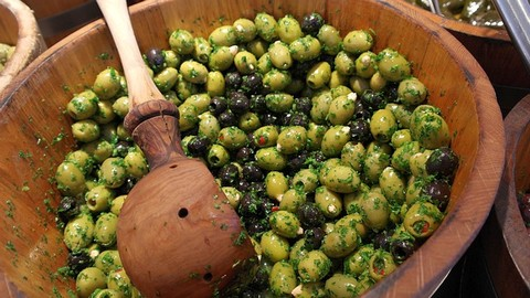 Pikcled olives in wooden pan