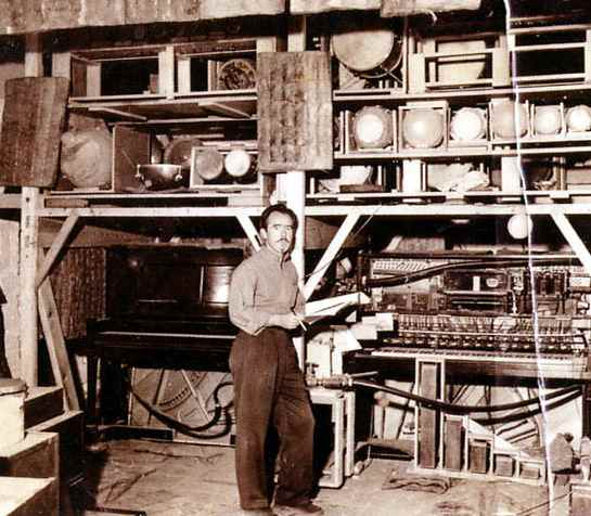 Conlon Nancarrow in his studio with player pianos and drums, 1940s