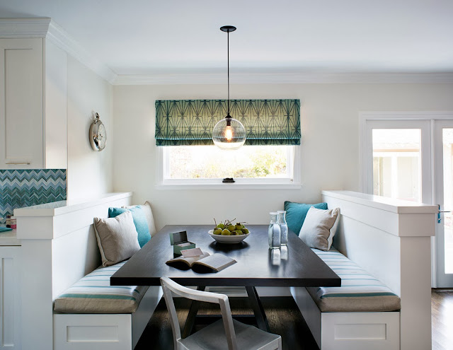 Breakfast nook with built in bench seating with blue and taupe accent pillows, a pendant light and roman shades