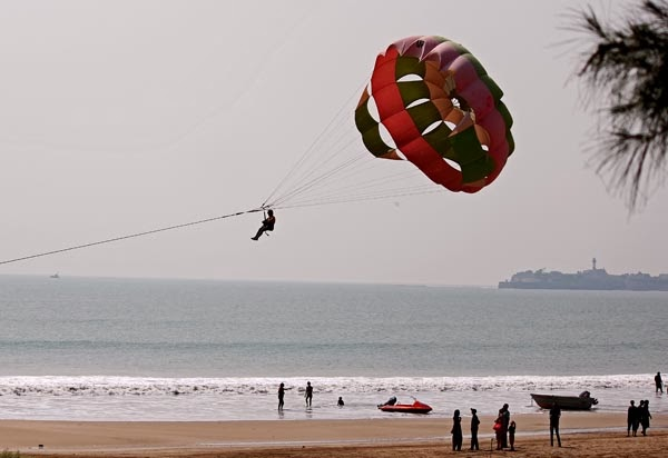 man para sailing on the beach in Diu