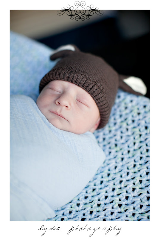 Baby boy wrapped in a blanet with a hat at lifestyle newborn portraits at William Jessup University in Rocklin, California