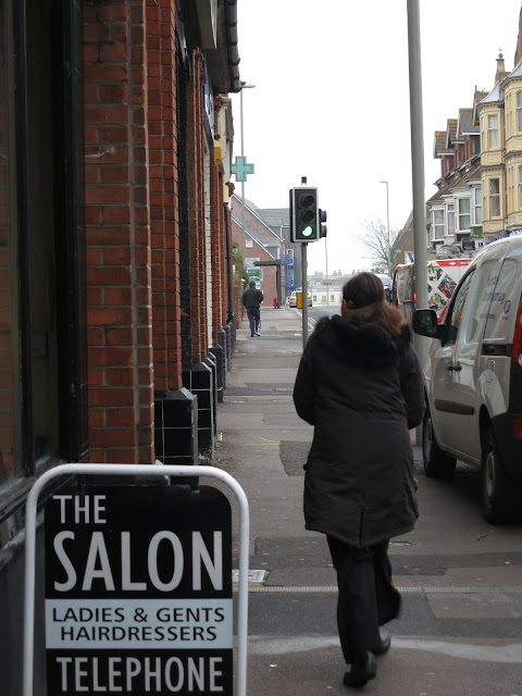 Woman walks down urban street past cars, lamposts and a hairdresser's sign.