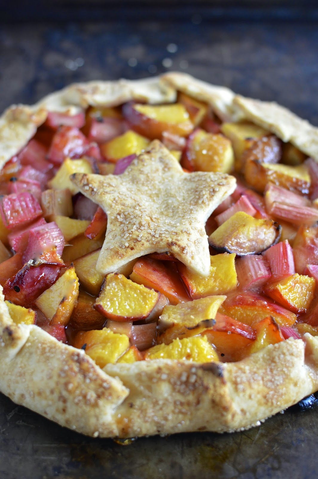 A brightly flavored vegan peach rhubarb crostata with vegan coconut whipped cream