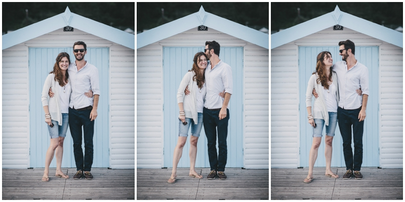 Engaged couple by beach huts