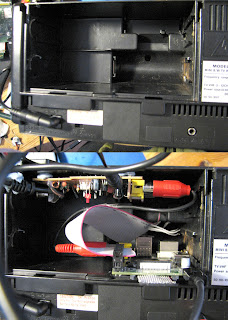 [Image: Two photos showing a big battery compartment, empty in the first picture and filled with electronics in the second one, with several wires coming out.]