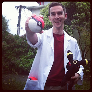 Josh, holding a Pokeball and a toy Pokemon, wearing a lab coat and a big smile.