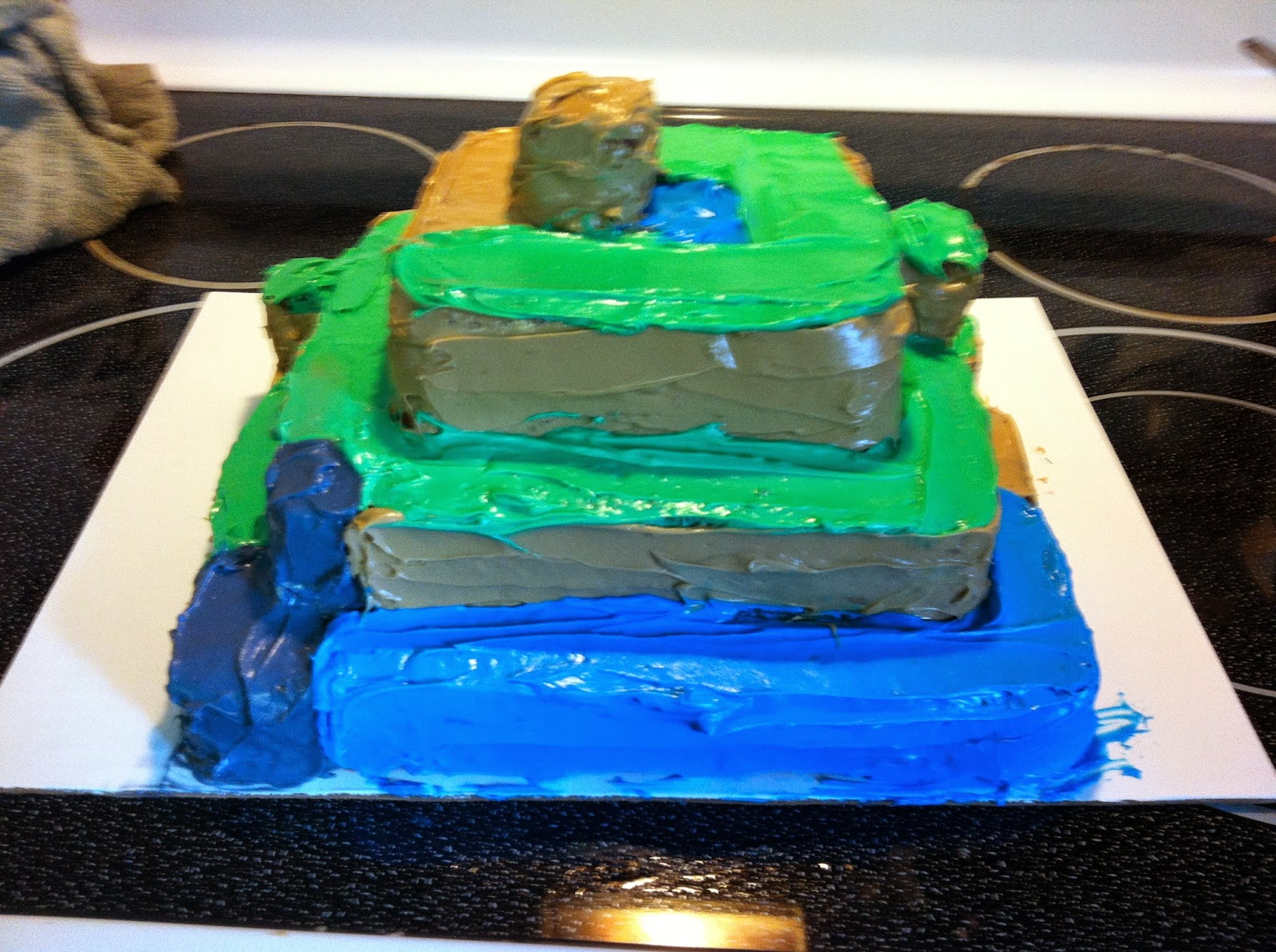 Minecraft cake side 3, featuring water, stone to the side, and a grassy hill.