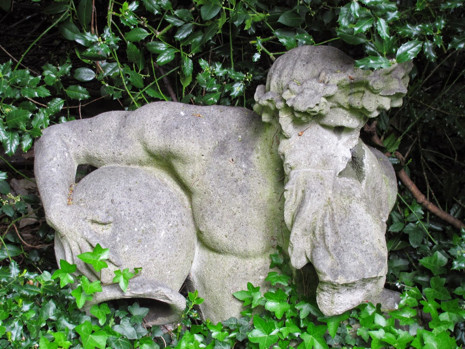 Ivy growing over a broken statue of a Greek god at Iveagh Gardens, Dublin