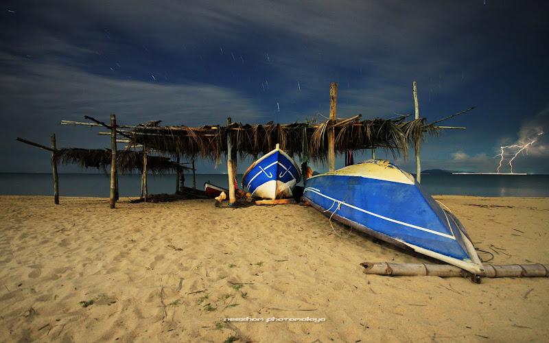 Bangsal simpan perahu dan kilat di tepi pantai Bisikan Bayu