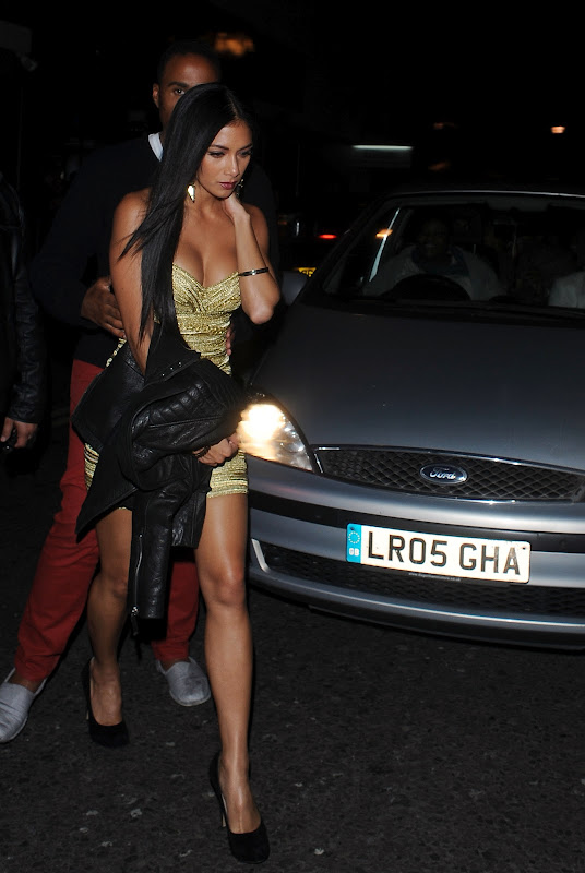 Nicole Scherzinger wearing a gold low cut dress and black heels