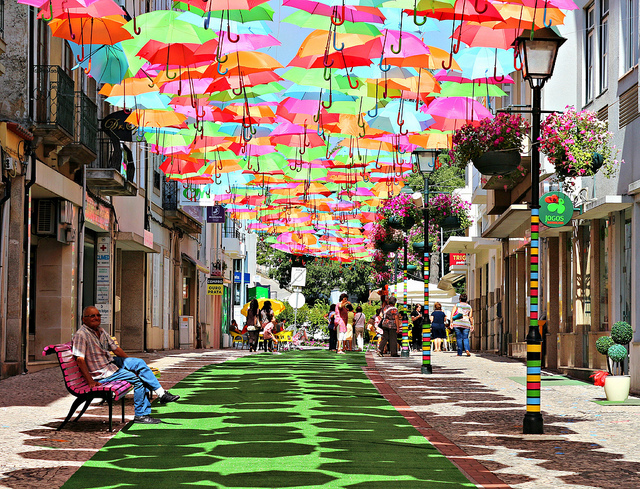 a man sitting on a bench on a street covered with colorful umbrellas in portugal