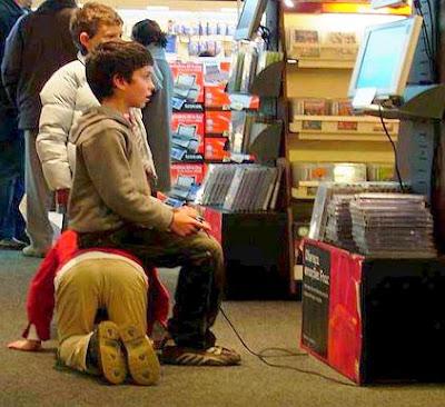 Garoto sacana usa amigo como banquinho para jogar video game.