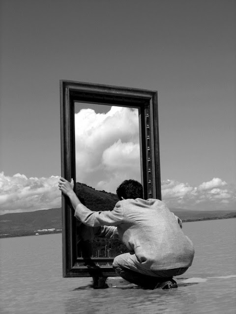 Man crouched in front of mirror in sea