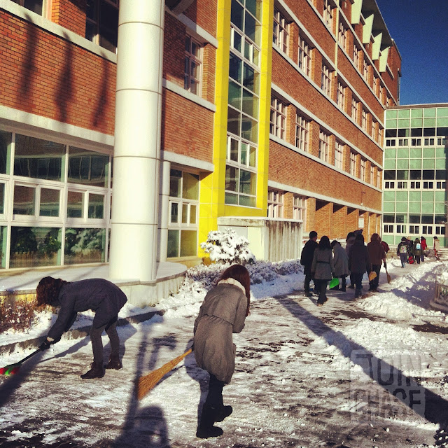 Teachers sweeping snow before school starts at Bibong Elementary in Ochang, South Korea.