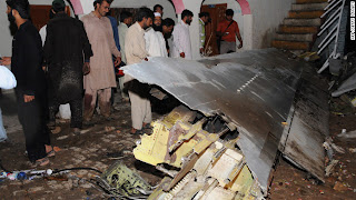 Pakistani villagers survey debris from the crash