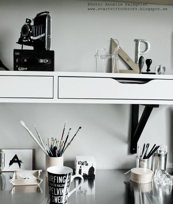 arbetsrum, arbetsrummet, ateljé, penslar i burk, blockkub med motiv, vykort, konsttryck, skrivbordsdetaljer, detaljer, gammal kamera som dekoration, ghost stol, miniatyrstol, stämplar, stämpel, svartvit mugg med text, varbergsmotiv,