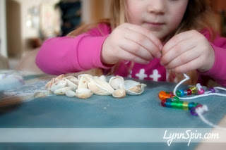 girl making shell necklace