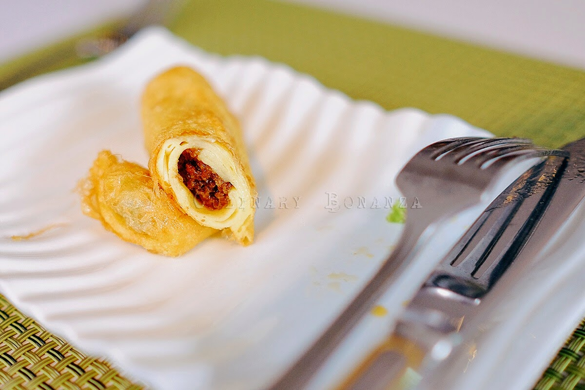 Sosis Solo - fried egg crepe with sweet and minced beef filling, served with sprayable chili oil