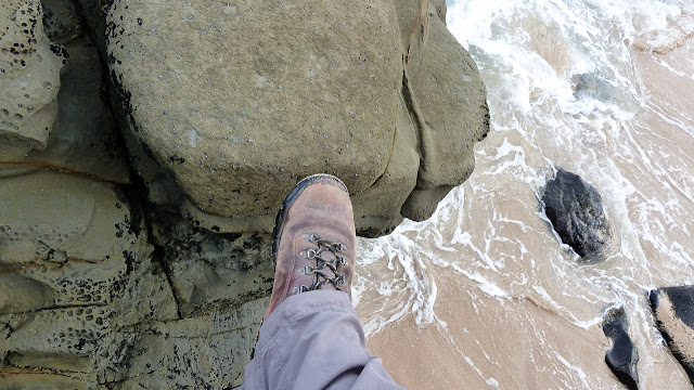 stepping across gap in rocks above beach