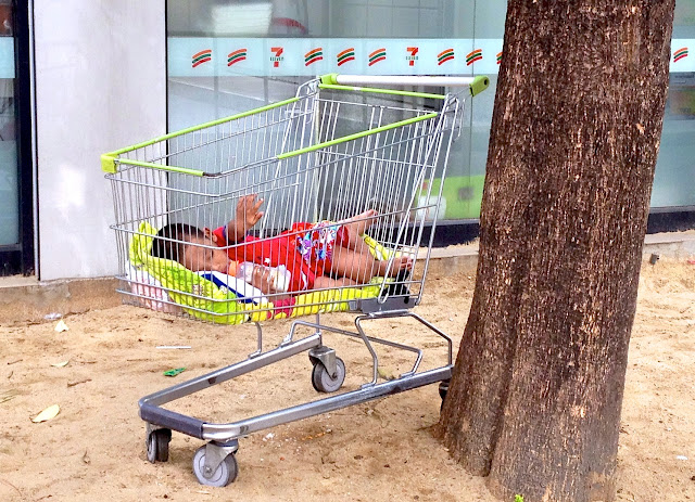 Child in a cart near Big C in Bangkok