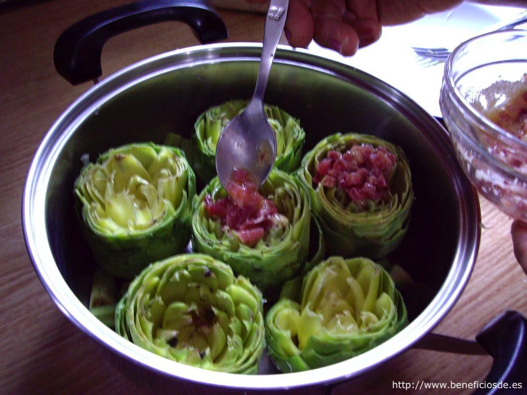 rellenando las alcachofas con jamón