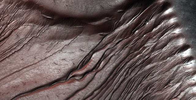 The study looked at gullies like these in Russell Crater, shown with winter CO2 frost accumulating. Credit: NASA/JPL/University of Arizona