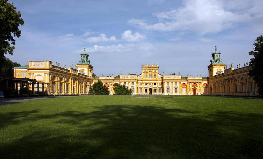 Foto frontal do palácio com o enorme campo relvado em primeiro plano