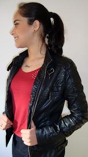 Jaqueta de couro, cabelo preso e acessórios pequenos e sem brilho.