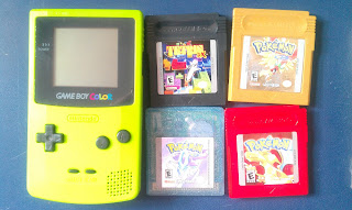 a green game boy color and four games: Tetris, Pokemon Gold, Pokemon Crystal, and Pokemon Red