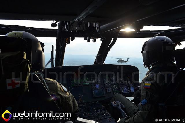 Pilotos de la Fuerza Aérea Colombiana mantienen formación cerrada con un UH-60 Black Hawk.