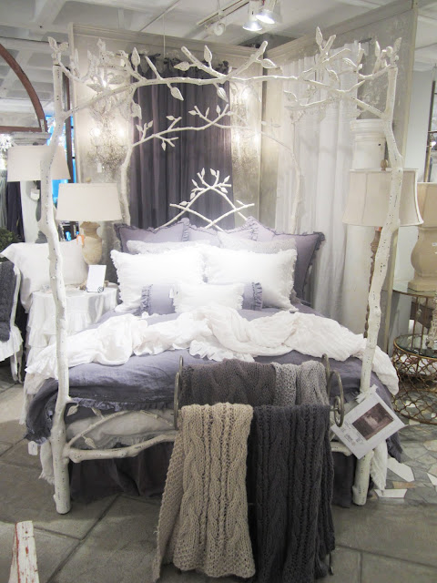 Metal bed frame painted white to look like birch trees by Corsican with chunky purple and white knit throws and matching bedding