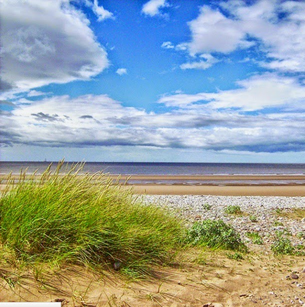 Sandy beach on North Wales. Blue sky, white clouds and sunshine. Beach grass and pebbles along the british coast.