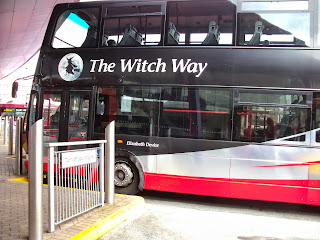 A double-decker bus of the 'Witch Way' route, with a flying witch painted in the side, and the name 'Elizabeth Device'.
