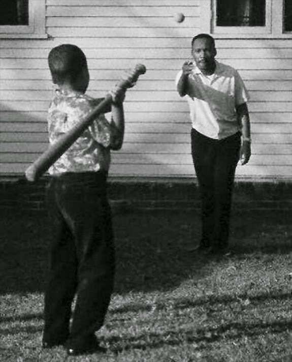 Martin Luther King Jr. at home playing baseball with his son.