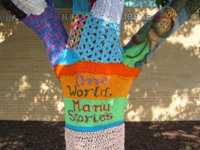 Tree trunk covered in knit and crocheted swatches of many colors. Across a panel circling the trunk, four words are centered in four lines of text: 'One World. Many Stories.'
