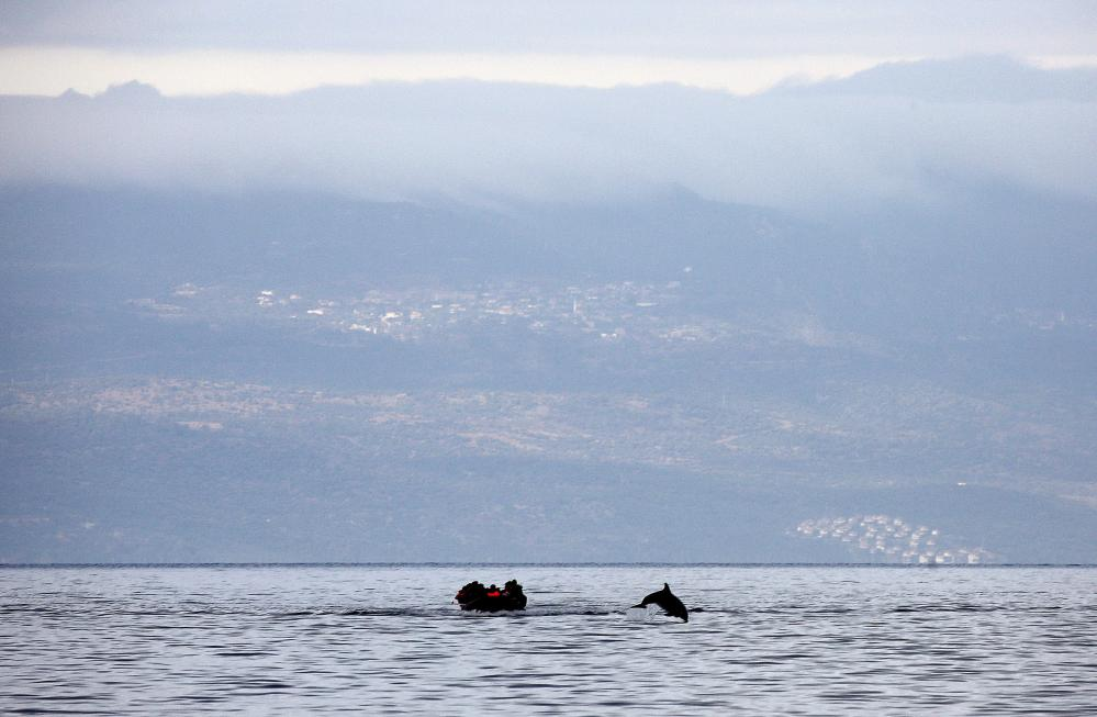 70 Of The Most Touching Photos Taken In 2015 - A dolphin jumping next to the refugees' raft