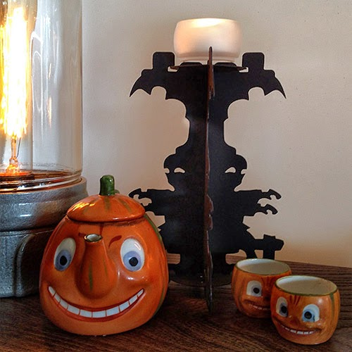 Paper decoration by artist Bindlgrim features ghost silhouettes and is shown with an antique German Jack O'Lantern tea set.