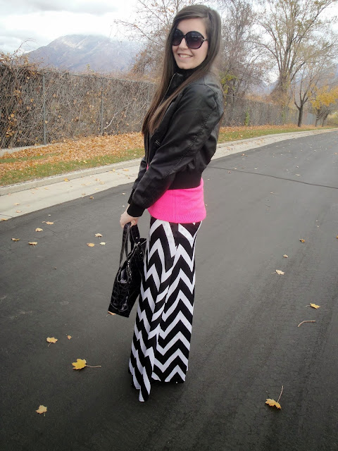 chevron skirt, pink sweater, leather jacket, pop of color, bag, long hair,