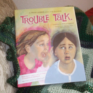 Photo of a book,Trouble Talk by Trudy Ludwig, illustrated by Mikela Prevost, on top of a folded, crocheted green zig-zag afghan