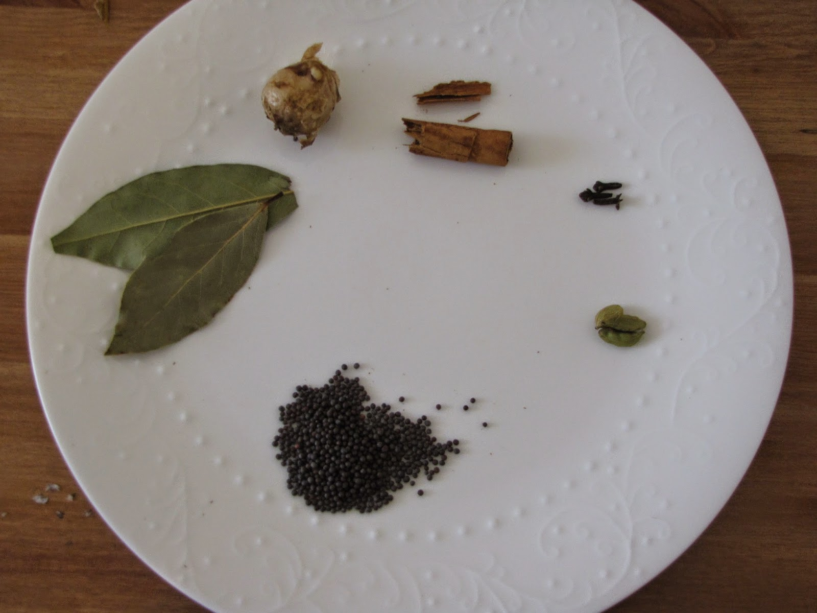 Bay leaves, ginger, cinnamon, cloves, cardamon pods and mustard seeds on a white plate