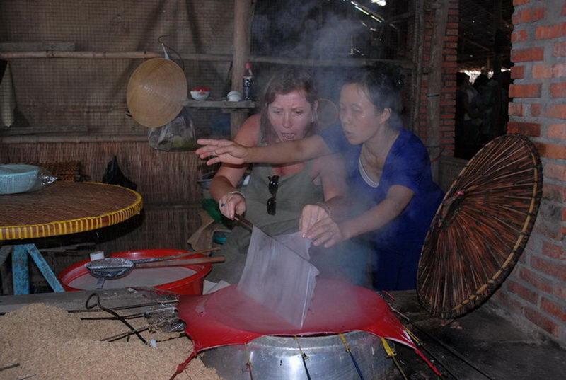 Du khách đang thử làm bánh tráng truyền thống