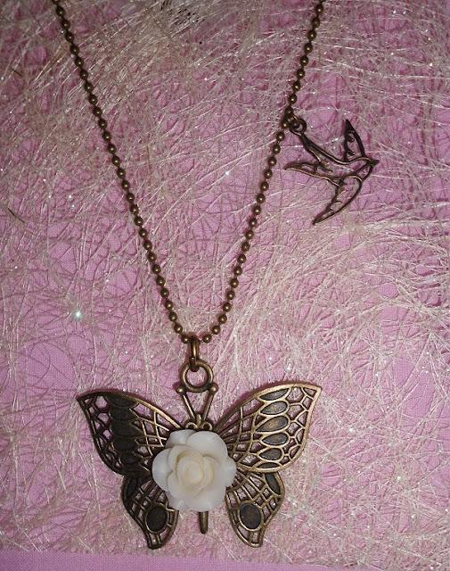 colgante mariposa con rosa marfil y con detalle de una golondrina