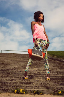 model stands on stairs with floral print trousers and pink vest wearing Louboutin shoes