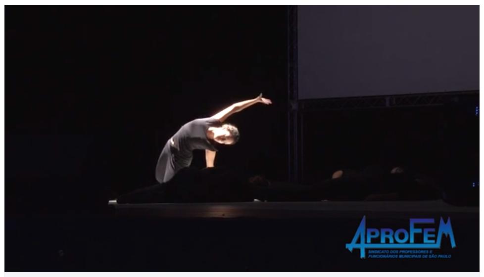 Descrição da Foto: Intérprete está ajoelhada com um braço apoiado no chão o outro esticado para cima, formando uma curva com seu corpo sobre um foco de luz branca.