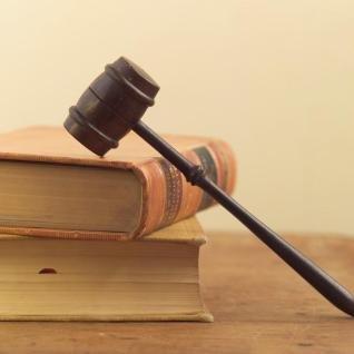Mazo de juez apoyado sobre una pila de libros.
