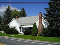 modelo de casa un piso blanca con chimenea rodeada de arbustos