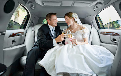 A newlywed couple sits inside Chicago limo drinking champagne